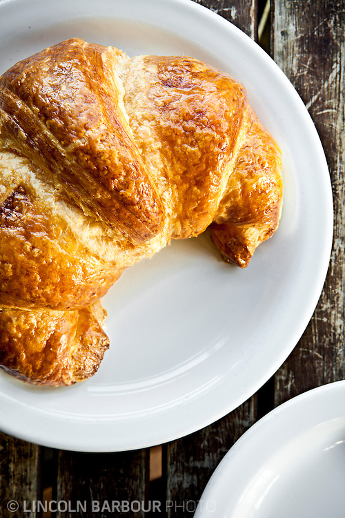 Overhead shot of a croissant on a white plate