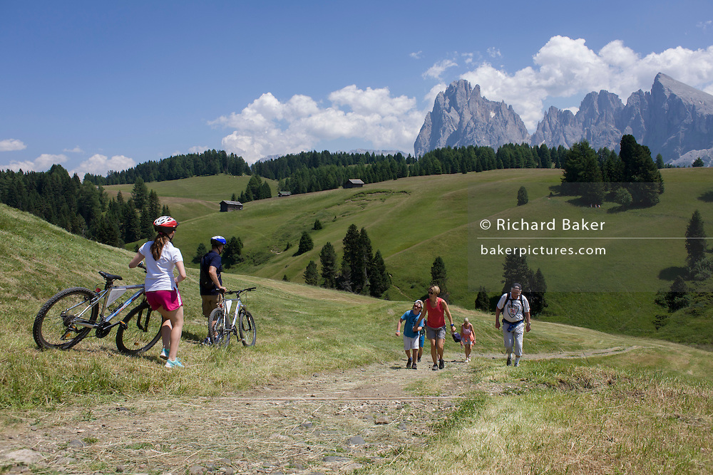 Hikers on the Siusi plateau, above the South Tyrolean town of Ortisei-Sankt Ulrich in the Dolomites, Italy.