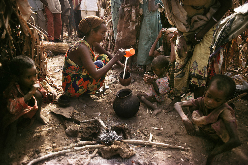 Refugees around a cooking fire in a refugee camp near Merca, 100 km. south of Mogadishu, the war-torn capital of Somalia. March 1992.