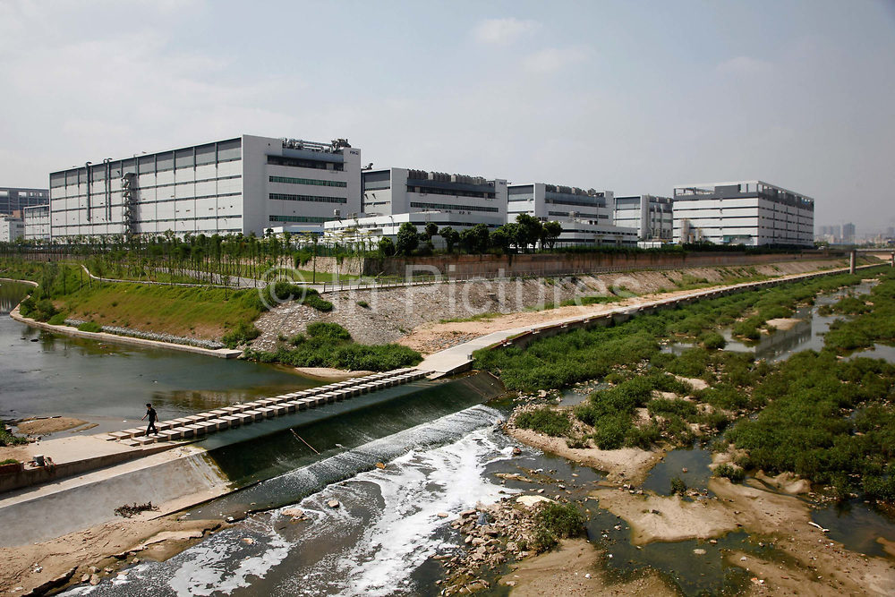 Workers walk outside Hon Hai Group's Foxconn plant, surrounded by a moat like canal system, in Shenzhen, China, on Wednesday, May 26, 2010. Hon Hai is the parts supplier for many hi-tech companies around the world including Apple Inc., Hewlett-Packard Co. and Dell Inc. There have been 12 suicides at the company's 300 thousand employee strong factory complex in Shenzhen so far this year. Foxconn has since moved some of its operations further inland to be closer to labor pool as well as cut costs.