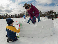 Chester Behner adds a splash of color while Louisa and her mother Katie Behner continue to build blocks on their snow fort during Winter Fest Saturday afternoon at Prescott Farms.   (Karen Bobotas/for the Laconia Daily Sun)