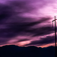 Electric polls and wires in front of sun in purple clouds with mountains in the back ground.