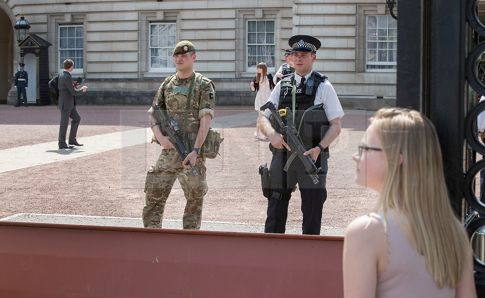 © Licensed to London News Pictures. 24/05/2017. London, UK. A tourist (R) looks on as a soldier stands with policeman on guard duty at Buckingham Palace. The terrorism threat level has been raised to critical and Operation Temperer has been deployed. 5,000 troops are taking over patrol duties under police command. Photo credit: Peter Macdiarmid/LNP
