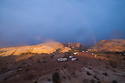 Rainbow at sunrise over a campground tucked away in the sandstone formations of the San Rafael Swell, Utah.
