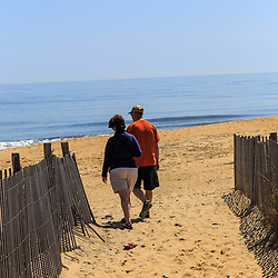 Bethany Beach, DE / USA - April 18, 2015: A man, woman, and their dog walk to the beach in Bethany, Delaware.