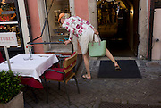A lady shopper stretches to see down a lower-level floor in the northern Italian south Tyrolean city of Bozen-Bolzano.