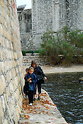 Woman and two children walking at base of stone wall, opposite Fortress Bokar, Dubrovnik old town, Croatia