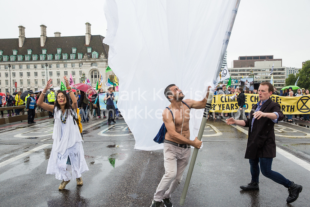 London, UK. 19 July, 2019. Climate activists from Extinction Rebellion cross Westminster Bridge in heavy rain on a march from their camp at Waterloo Millennium Green to Parliament Square on the fifth day of their 'Summer uprising' to call on local and central government to take urgent steps to address the climate emergency.