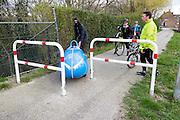 Ligfietsers moeten voorbij een hek dat op het fietspad in Kesteren is geplaatst tegen racefietsers. In Woudenberg houdt de ligfietsvereniging NVHPV het jaarlijks paastreffen met onder andere een fietstocht. <br /> <br /> In Woudenberg the Dutch recumbent society is having its early eastern meeting with a tour ride.