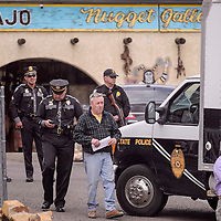 Steve Coleman, center, walks with New Mexico State Police officers in the parking lot of The Nugget Gallery in Gallup Tuesday.