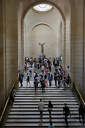 Tourists walk towards The Winged Victory of Samothrace, also called the Nike of Samothrace, a 2nd century BC marble sculpture of the Greek goddess Nike (Victory). Since 1884, it has been prominently displayed at the Louvre and is one of the most celebrated sculptures in the world.