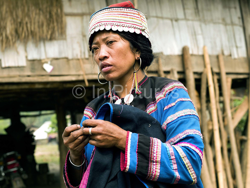 A Mounteun ethnic minority woman sews her traditional clothing outside her home in Ban Mounteun, Phongsaly province, Lao PDR. One of the most ethnically diverse countries in Southeast Asia, Laos has 49 officially recognised ethnic groups although there are many more self-identified and sub groups. These groups are distinguished by their own customs, beliefs and rituals. Details down to the embroidery on a shirt, the colour of the trim and the type of skirt all help signify the wearer's ethnic and clan affiliations.
