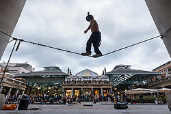 © Licensed to London News Pictures. 23/10/2020. LONDON, UK. A street performer entertains the public in the piazza in Covent Garden.  Shaftesbury, owner of 16 acres of land in the capital including Chinatown, parts of Soho and Covent Garden, has announced emergency plans to raise almost £300m to help it survive the coronavirus pandemic as tourists and workers stay away from the West End. The property firm is struggling to collect rent from its retail, restaurant and bar tenants, who have had persistently lower footfall and trade.  Photo credit: Stephen Chung/LNP