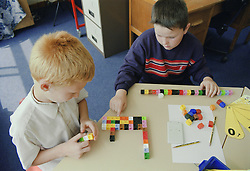 Primary school boys using unilink blocks and number fans in practical maths lesson,