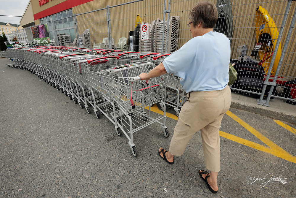 Woman removing/returning a shopping cart from/to a stack of carts., Greater Sudbury , Ontario, Canada