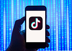 Person holding smart phone with  TikTok  logo displayed on the screen. TikTok is a media app for creating and sharing short videos EDITORIAL USE ONLY