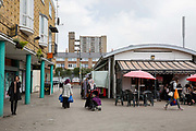 Balfron Tower, from Chrisp Street Market, on 27th April 2016 in London, United Kingdom. The architecturally important Balfron Tower is a 26-storey residential building in Poplar, a district of the London Borough of Tower Hamlets in the East End of London. It was designed by Ernő Goldfinger and built in a brutalist style for the London Country Council. It and opened in 1967. The tower forms part of the Brownfield Estate. It has been a Grade II listed building since 1996. Balfron Tower is stylistically similar to Goldfingers later Trellick Tower in West London. Recently, residents and campaigners are battling to prevent a regeneration of the celebrated tower.