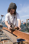 Boat restorer Christian Chaves planing the edge of a plank at the New England Shipyard in North Kingstown, Rhode Island.
