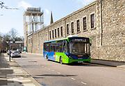 Single decker Swindon bus company vehicle passing old railway works, Swindon, Wiltshire, England, UK