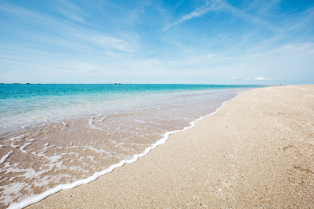 Crystal clear, turquoise water on the shoreline of the sandbanks at the Minquiers, a tropical paradise in Jersey, Channel Islands