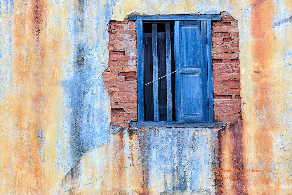 Weathered: A partially shuttered window, with various coloured dies forming streaks down the weathered wall, in Savannakhet Laos.