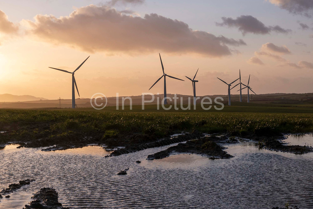 Waves form across a puddle in front of wind turbines on Llyn Alaw Wind Farm in full electricity production during the tail end of Storm Dennis on 17th February 2020 in Anglesey, Wales, United Kingdom. Llyn Alaw Wind Farm is located on Anglesey in North Wales, it consists of 34 turbines with a capacity of 20.4 MW mega watts and can produce an average 60,000 kilowatt hours KWh each year. This is enough to provide electricity for 14,000 homes in the local community.