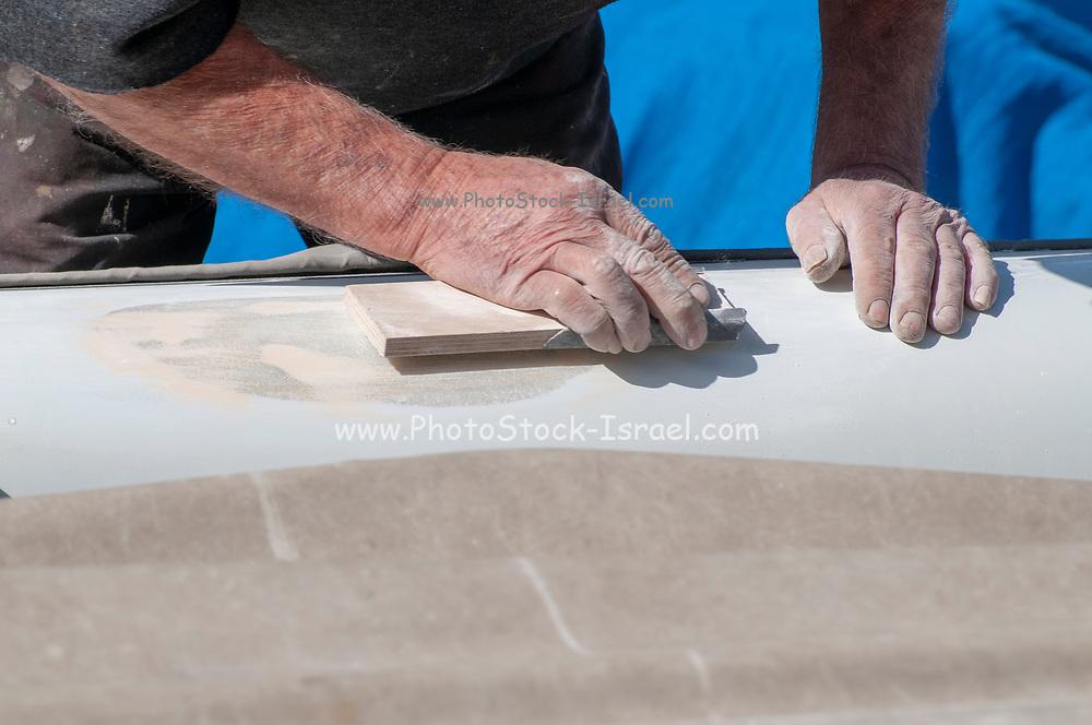 Man fixes a fiberglass boat