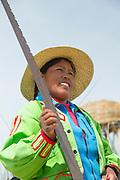 Native Uru woman with saw on the Floating islands of Lake Titicaka, Puno, Peru, South America
