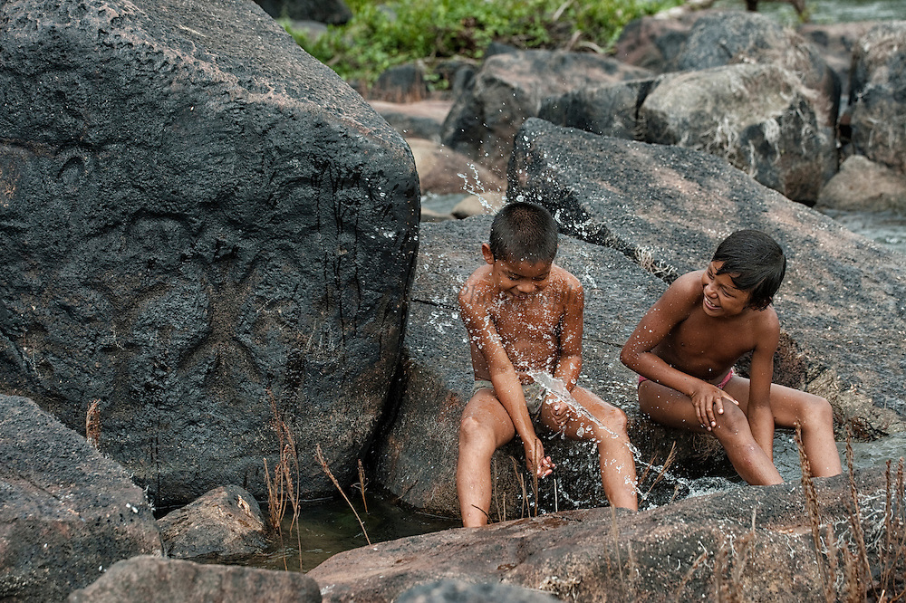 Ancient Petroglyphs (Rock carvings) & Amerinidian Children<br /> Exposed at low river levels these carvings are thought to be at least 10,000 years old.<br /> Fairview Amerindian Village<br /> Iwokrama Forest Reserve<br /> GUYANA<br /> South America