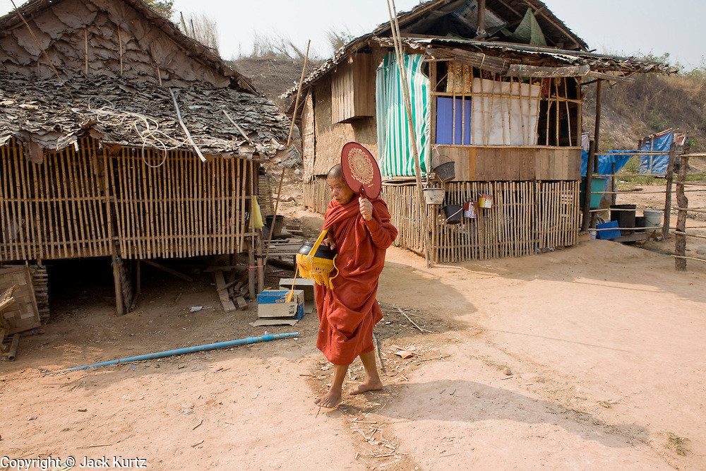 26 FEBRUARY 2008 -- MYAWADDY, MYANMAR: A monk walks through a neighborhood in Myawaddy, Myanmar. Myawaddy is just across the Moei River from Mae Sot, Thailand and is one of Myanmar's leading land ports for goods going to and coming from Thailand. Most of the businesses in the town are geared towards trade, both legal and illegal, with Thailand. Human rights activists from Myanmar maintain that the Burmese government controls the drug smuggling trade between the two countries and that most illegal drugs made in Myanmar are shipped into Thailand from Myawaddy.   Photo by Jack Kurtz