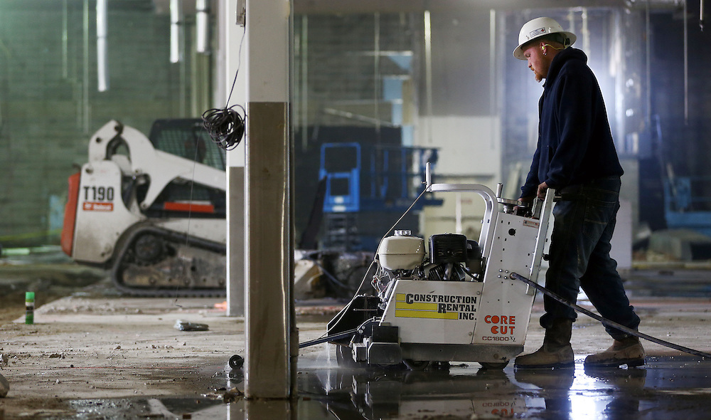 Levi VanMark of Bigzby's Concrete cuts part of the floor while working on renovations Wednesday at the former Furniture Super Center at Highway 281 and State Street. Bed Bath & Beyond, Shoe Carnival and Dress Barn will be located in the renovated building to be completed by the fall. (Independent/Matt Dixon)