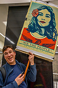 """San Francisco, California, USA. 21st January, 2017. Man holds sign """"We the people"""" with image by artist Shepard Fairey in San Francisco BART station before women's march 2017. Credit: Shelly Rivoli"""
