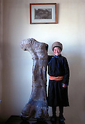 A school boy on a class tour stands proud with a sauropod femur on display at the Ulan Bator State Museum in Mongolia.<br /> A school boy in a tradional dell (or deel) on a class tour stands proud with a sauropod femur on display at the Ulan Bator State Museum in Mongolia.