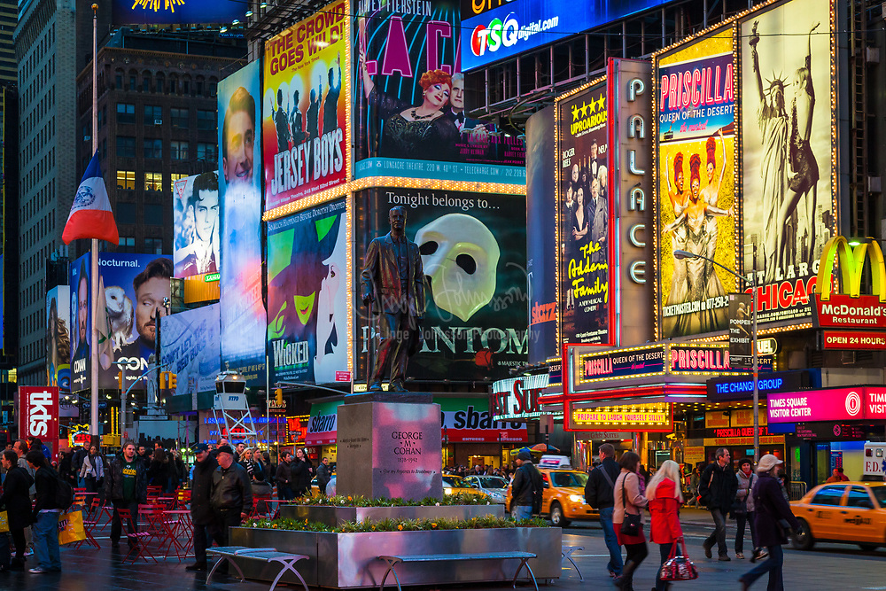 """Billboards for Broadway shows in Times Square, New York City. Times Square is a major commercial intersection and neighborhood in Midtown Manhattan, New York City, at the junction of Broadway and Seventh Avenue, and stretching from West 42nd to West 47th Streets. Brightly adorned with billboards and advertisements, Times Square is sometimes referred to as The Crossroads of the World, The Center of the Universe, the heart of The Great White Way, and the """"heart of the world"""". One of the world's busiest pedestrian intersections, it is also the hub of the Broadway Theater District and a major center of the world's entertainment industry. Times Square is one of the world's most visited tourist attractions, drawing an estimated 50 million visitors annually. Approximately 330,000 people pass through Times Square daily, many of them tourists, while over 460,000 pedestrians walk through Times Square on its busiest days."""
