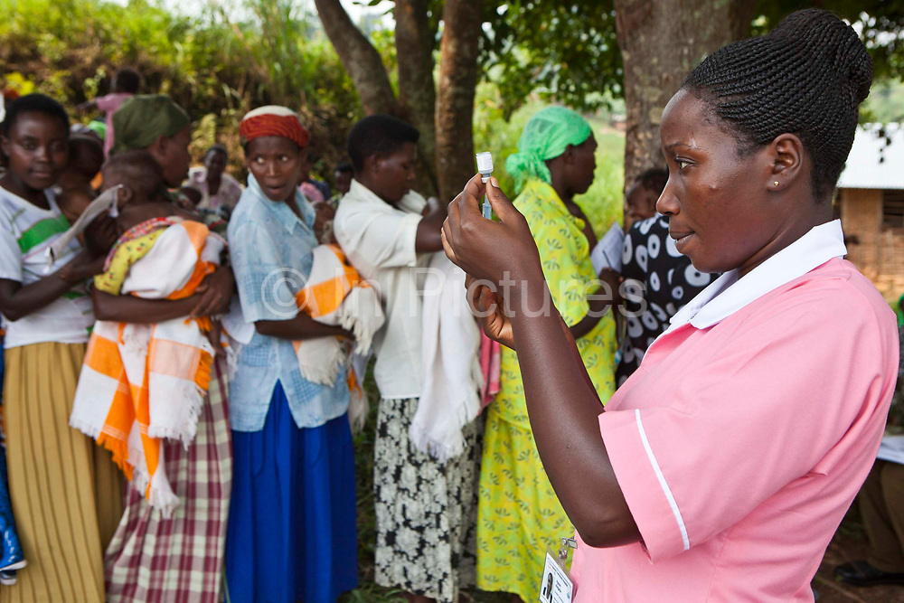 Nurse Agnes from Bwindi Community hospital prepares and administer the vaccination program during the out reach clinic in Kitahurira, the only Batwa tribe settlement in Mpungu district.  She administers Polio and measles vaccinations to newborn children in the community.