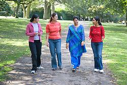 Four friends; walking in the park; talking,