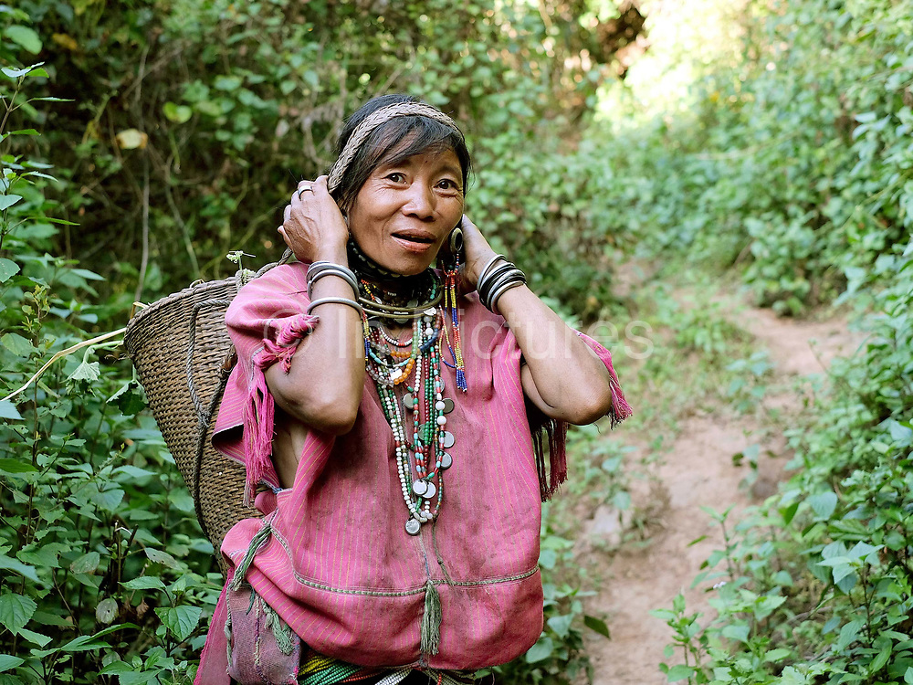 An ethnic minority Kayaw woman wearing her traditional costume walking back from an upland rice field in Yo Co Pra village in Kayah State, Myanmar on 21st November 2016