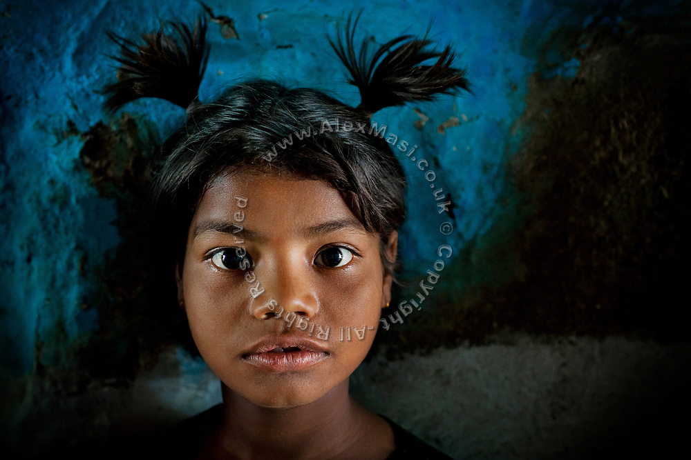 Poonam, 9, is standing inside her old, rundown home (where she lived until June 2011) on the day Alex and the young girl have met again, after his image of her revelling under the heavy rain was granted 5000 US dollars by 'The Photographers Giving Back Awards', in Sweden, destined towards her wellbeing, in Oriya Basti, one of the water-contaminated colonies in Bhopal, central India, near the abandoned Union Carbide (now DOW Chemical) industrial complex, site of the infamous '1984 Gas Disaster'.