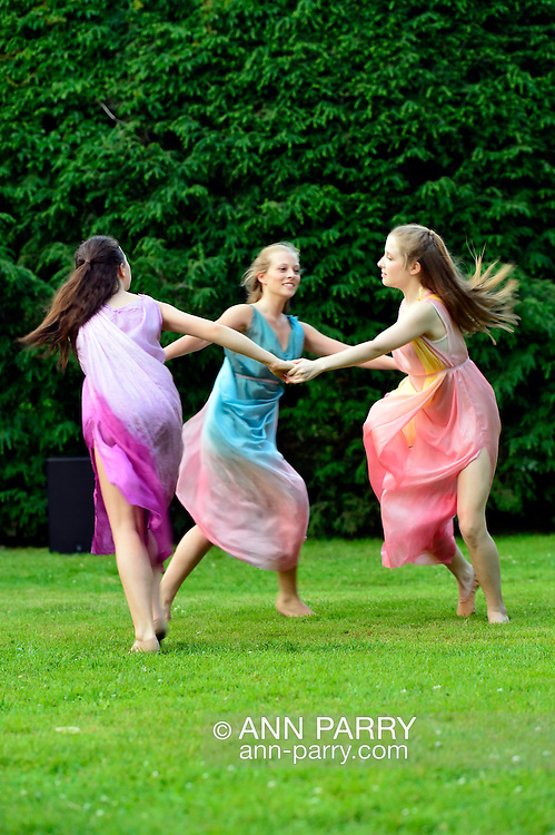 Old Westbury, New York, U.S. 22nd June 2013. Dancers in Lori Belilove & The Isadora Duncan Dance Company, whirl in a circle during a dance of the Three Graces, at the Midsummer Night event at Old Westbury Gardens, throughout the illuminated grounds of the historic Long Island Gold Coast estate.<br />