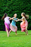 Old Westbury, New York, U.S. 22nd June 2013. Dancers in Lori Belilove & The Isadora Duncan Dance Company, whirl in a circle during a dance of the Three Graces, at the Midsummer Night event at Old Westbury Gardens, throughout the illuminated grounds of the historic Long Island Gold Coast estate.<br /> The Three Graces, or Three Charities, of Greek mythology were Aglaia, Euphrosyne, and Thalia - goddesses of beauty, joy, harmony, pleasure, grace, festivity, adornment, dance, and song. Daughters of Zeus and sea-nymph Eurynome, they were also the attendants, or handmaidens, of Aphrodite and Hera and protectors of vegetation.