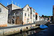 Derelict buildings and houses with canal and bridge, village of Vrboska, island of Hvar, Croatia