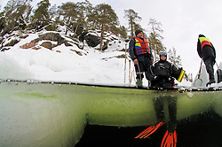 split shot from ice diving, ice diver sitting on the ice hole, Russia,  White Sea, MR