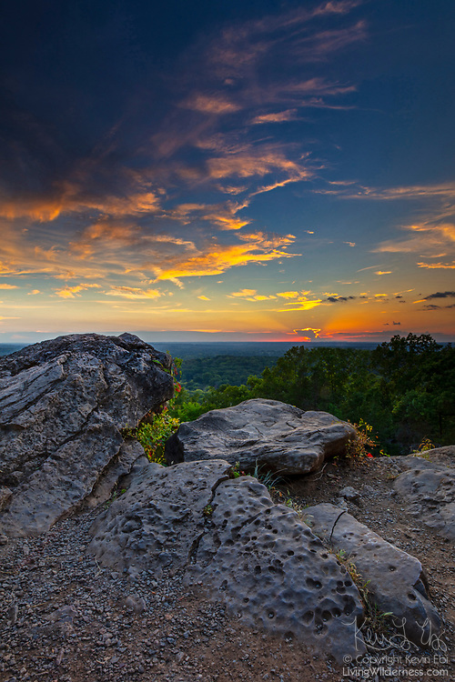 Cirrus clouds, turned golden by the setting sun, fill the sky above the summit of Ruffner Mountain in Birmingham, Alabama.