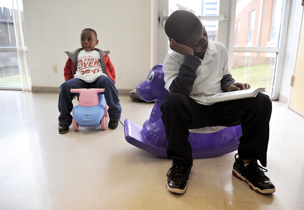 JaJuan reads in the Salvation Army playroom while his little brother Mythias plays on a toy car.
