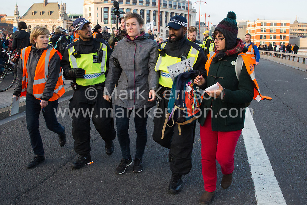 London, UK. 17th November, 2018. Police officers arrest a woman after environmental campaigners from Extinction Rebellion blocked Blackfriars Bridge, one of five bridges blocked in central London, as part of a Rebellion Day event to highlight 'criminal inaction in the face of climate change catastrophe and ecological collapse' by the UK Government as part of a programme of civil disobedience during which scores of campaigners have been arrested.