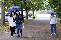 © Licensed to London News Pictures. 19/09/2021. London, UK. Members of the public shelter under umbrellas as they walk in Greenwich park during a rain shower. A yellow weather warning for rain is in place for parts of England.  Photo credit: George Cracknell Wright/LNP