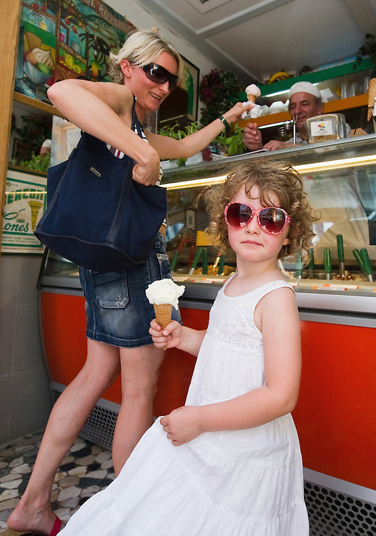 VENICE, ITALY - JUNE 30:Mother and daughter buy an ice cream from Carlo Pistacchi's Gelateria Alaska in Santa Croce on June 30, 2011 in Venice, Italy. Carlo has been making ice-cream using fresh ingredients for more than 25 years and is renowned for experimenting with new flavours, offering his customers classic favourites such as rum and raisin or chocolate as well as some of his more unconventional creations such as asparagus or rocket salad and orange.