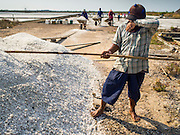 09 MARCH 2015 - NA KHOK, SAMUT SAKHON, THAILAND: A man stacking salt during the salt harvest wipes his brow. The coastal provinces of Samut Sakhon and Samut Songkhram, about 60 miles from Bangkok, are the center of Thailand's sea salt industry. Salt farmers harvest salt from the waters of the Gulf of Siam by flooding fields and then letting them dry through evaporation, leaving a crust of salt behind. Salt is harvested through dry season, usually February to April. The 2014 salt harvest went well into May because the dry season lasted longer than normal. Last year's harvest resulted in a surplus of salt, driving prices down. Some warehouses are still storing salt from last year. It's been very dry so far this year and the 2015 harvest is running ahead of last year's bumper crop. One salt farmer said prices are down about 15 percent from last year.    PHOTO BY JACK KURTZ