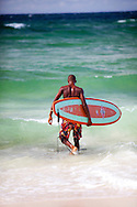 Zed's surf school at Surfer's Point on the South Coast of Barbados.  A young surf instructor heads out to sea to teach a lesson.