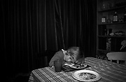 A 3 year-old girl falls asleep before finishing her dinner, the food of which is still on the plate under her head, at home in her south London home. It is early evening and it has been a busy, tiring day that has ended rather suddenly over the dinner plate. Heavy felt curtains are drawn to block out the winter's night and the remains of her tea and half-drunk drink is on the table cloth.